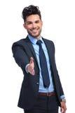 El hombre de negocios sonriente le está acogiendo con satisfacción con una sacudida de la mano Fotos de archivo libres de regalías