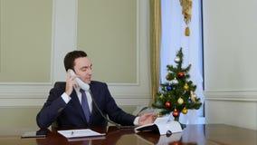 El hombre de negocios sonriente que coge el teléfono y felicita a colegas del negocio con la Navidad almacen de video