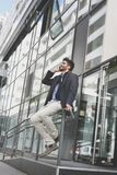 El hombre de negocios sonriente se sienta delante del edificio y del talkin Fotos de archivo libres de regalías
