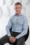 El hombre de negocios sonriente se sienta en oficina urbana moderna Foto de archivo libre de regalías