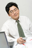 El hombre de negocios sonriente sostiene su móvil Imagenes de archivo