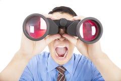 El hombre de negocios sorprendido mira a través de los prismáticos Foto de archivo libre de regalías