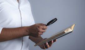 El hombre de negocios sostiene la lupa y el libro fotos de archivo