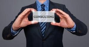 El hombre de negocios sostiene la tarjeta blanca con la muestra asesor, gris - acción Imagenes de archivo