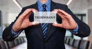 El hombre de negocios sostiene la tarjeta blanca con la muestra de la tecnología, acción de la oficina Foto de archivo libre de regalías