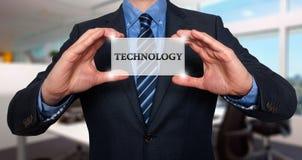 El hombre de negocios sostiene la tarjeta blanca con la muestra de la tecnología, acción de la oficina Imagen de archivo libre de regalías