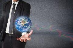El hombre de negocios sostiene la tierra en una mano con el gráfico común Concepto de r Imagen de archivo libre de regalías