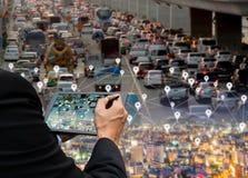 El hombre de negocios sostiene un coche de la tableta en la tecnología de la red de carreteras del mapa digital fotos de archivo libres de regalías