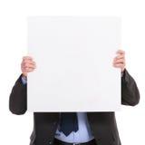 El hombre de negocios sostiene un panel delante de su cara Imágenes de archivo libres de regalías
