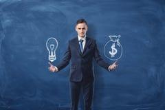 El hombre de negocios sostiene una bombilla en una mano y un bolso del dinero en otra mano en fondo azul de la pizarra Foto de archivo