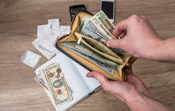 El hombre de negocios sostiene una cartera con los dólares en el cuaderno del fondo Fotografía de archivo libre de regalías