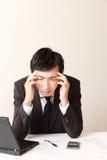 El hombre de negocios sufre de dolor de cabeza o de Asthenopia Foto de archivo libre de regalías