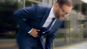 El hombre de negocios sufre del dolor de estómago agudo, gastritis, ardor de estómago, efecto mareado imagen de archivo libre de regalías