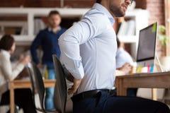 El hombre de negocios sufre de un dolor más de espalda que se sienta en oficina compartida imágenes de archivo libres de regalías