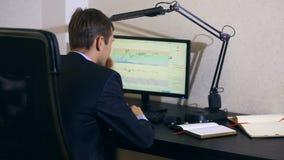 El hombre de negocios supervisa cambios en el horario en el intercambio de moneda, mirando el monitor de computadora almacen de video