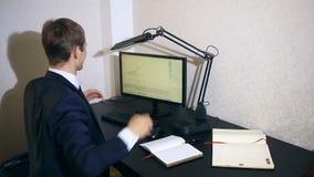 El hombre de negocios supervisa cambios en el horario en el intercambio de moneda, mirando el monitor de computadora metrajes