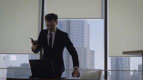 El hombre de negocios Talking On Phone en la ventana de la oficina entonces se sienta al lugar de trabajo almacen de metraje de vídeo