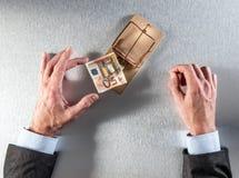 El hombre de negocios tentado da tomar un billete de banco para la pregunta de la inversión imagen de archivo libre de regalías