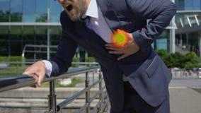 El hombre de negocios tiene ataque del corazón al aire libre, punto indica dolor en el pecho, primeros auxilios almacen de video