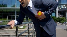 El hombre de negocios tiene ataque del corazón al aire libre, punto indica dolor en el pecho, primeros auxilios foto de archivo