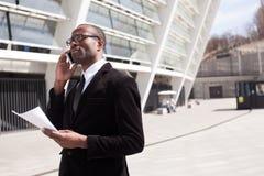 El hombre de negocios tiene conversación telefónica fotografía de archivo
