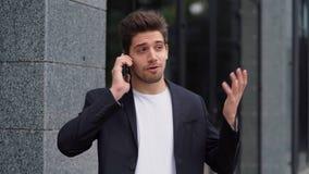 El hombre de negocios tiene conversación usando el teléfono móvil Individuo del negocio en del traje negociaciones formales con m metrajes