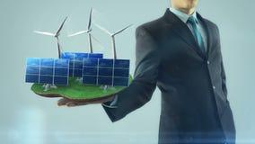 El hombre de negocios tiene a mano el panel solar y molino de viento de la energía del concepto de la animación verde de la estru almacen de video