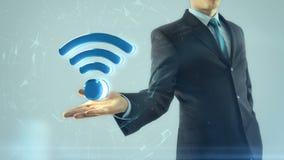 El hombre de negocios tiene a mano símbolo de la red del wifi almacen de video