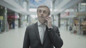El hombre de negocios tiene una conversación sobre el teléfono en el aeropuerto almacen de video