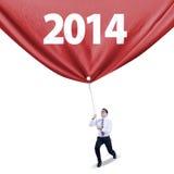 El hombre de negocios tira de la bandera del Año Nuevo Fotografía de archivo