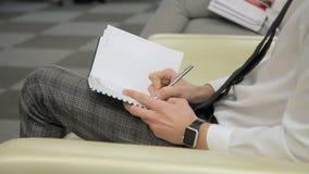El hombre de negocios toma notas sobre la conferencia usando su cuaderno y pluma en mano derecha metrajes