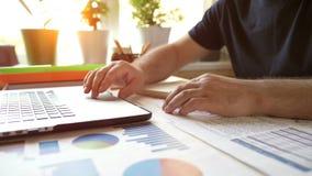 El hombre de negocios trabaja con el ordenador portátil en su lugar de trabajo en la oficina y analiza funcionamiento financiero metrajes