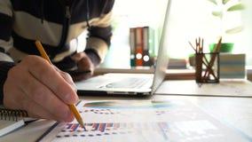 El hombre de negocios trabaja con un smartphone y la comprobación de informe y de cartas financieros en la oficina en el lugar de almacen de metraje de vídeo