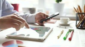 El hombre de negocios trabaja con una tableta y estudia la información financiera almacen de metraje de vídeo
