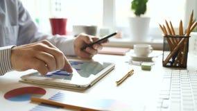 El hombre de negocios trabaja con una tableta y estudia la información financiera almacen de video