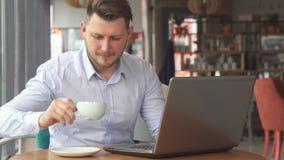 El hombre de negocios trabaja en el ordenador portátil en el café
