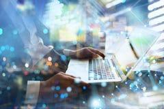 El hombre de negocios trabaja en oficina con un ordenador port?til con efectos de Internet Concepto de distribuci?n de Internet y imagen de archivo