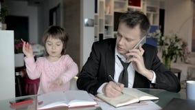 El hombre de negocios trabaja de hogar y toma cuidado de su pequeña hija almacen de metraje de vídeo