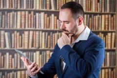 El hombre de negocios trabaja pensativamente en la tableta en la biblioteca Foto de archivo