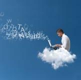 El hombre de negocios trabaja sobre una nube Foto de archivo