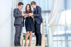 El hombre de negocios tres que se coloca en las escaleras soluciona problemas de negocio Imagen de archivo libre de regalías