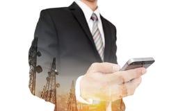 El hombre de negocios usando el teléfono elegante con paisaje urbano y la telecomunicación panorámicos de la exposición doble se  Fotografía de archivo libre de regalías