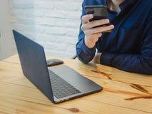 El hombre de negocios utiliza el teléfono y el labtop en la oficina Negocio, concepto del trabajo imagenes de archivo