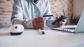El hombre de negocios utiliza un smartphone para las compras en línea, incorpora la información de la tarjeta de crédito almacen de metraje de vídeo