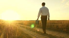 El hombre de negocios va en una carretera nacional con una cartera en su mano El empresario trabaja en una zona rural Un granjero almacen de metraje de vídeo