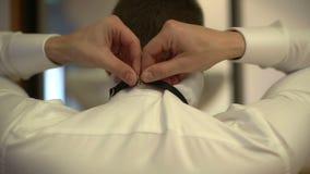 El hombre de negocios va a llevar una corbata de lazo a una reunión metrajes