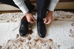 El hombre de negocios viste los zapatos, hombre que consigue listo para el trabajo, mañana del novio antes de la ceremonia de bod foto de archivo