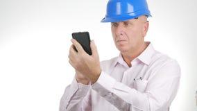 El hombre de negocios Wearing Engineer Helmet comunica usando el teléfono móvil foto de archivo libre de regalías