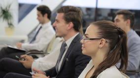 El hombre de negocios y la empresaria aumentaron sus manos que contestaban a la pregunta sobre el congreso de negocios almacen de video