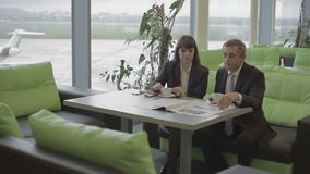 El hombre de negocios y la empresaria en el aeropuerto se preparan para subir almacen de video